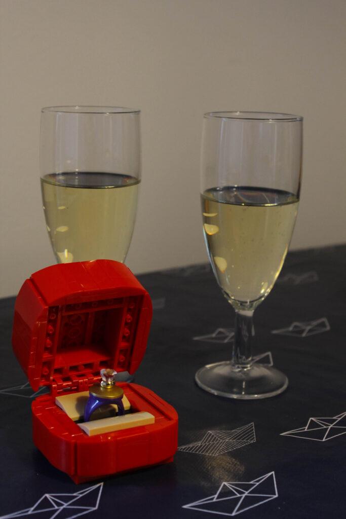 Forlovelsesring af LEGO og to glas champagne